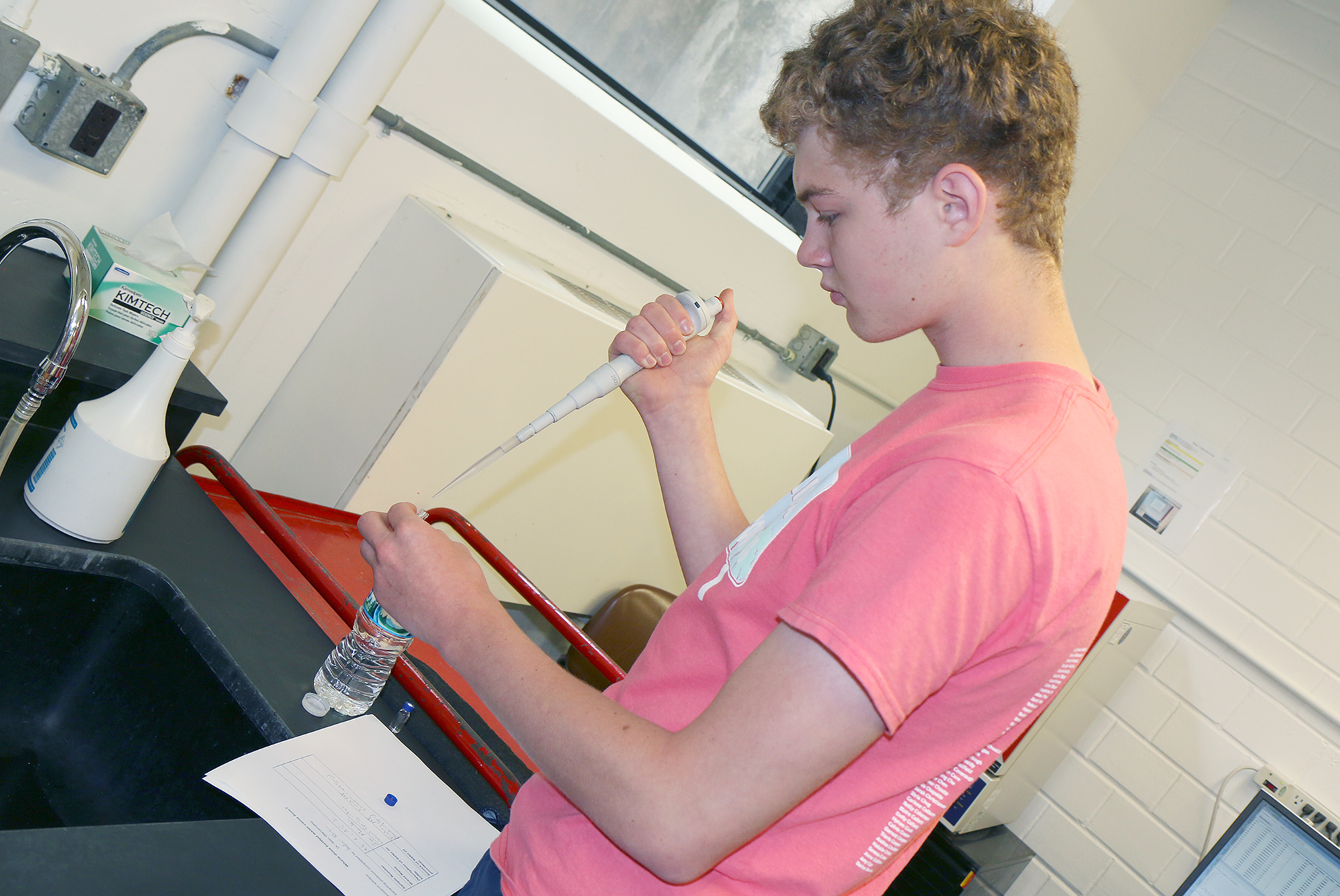 Student stands at a counter using a large pipette.