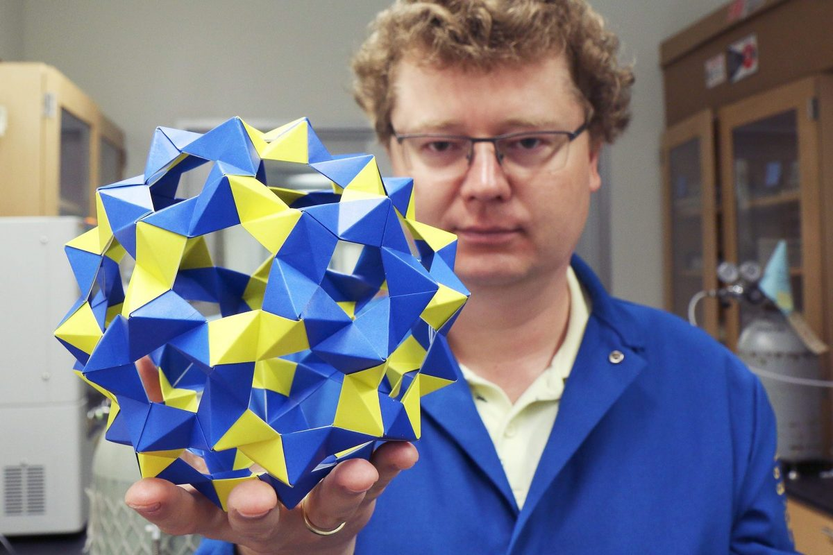 A paper spherical cage is held by Kirill Kovnir.