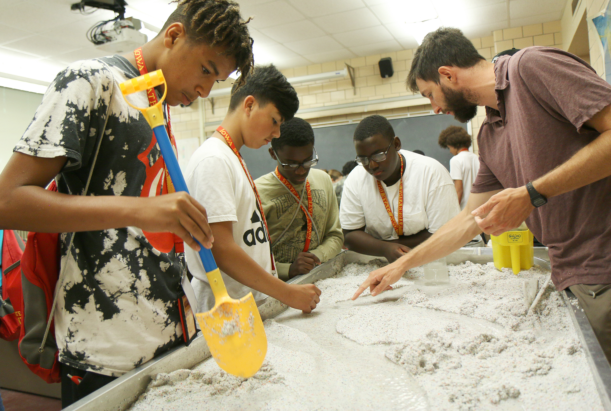 Students stand around a table filled with sand and a stream of water.