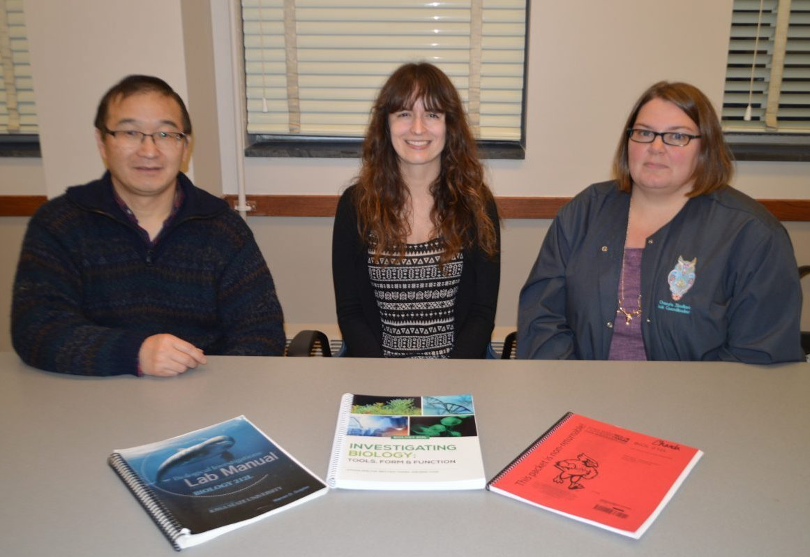 Three people sit at a table with three lab manuals in front of them.