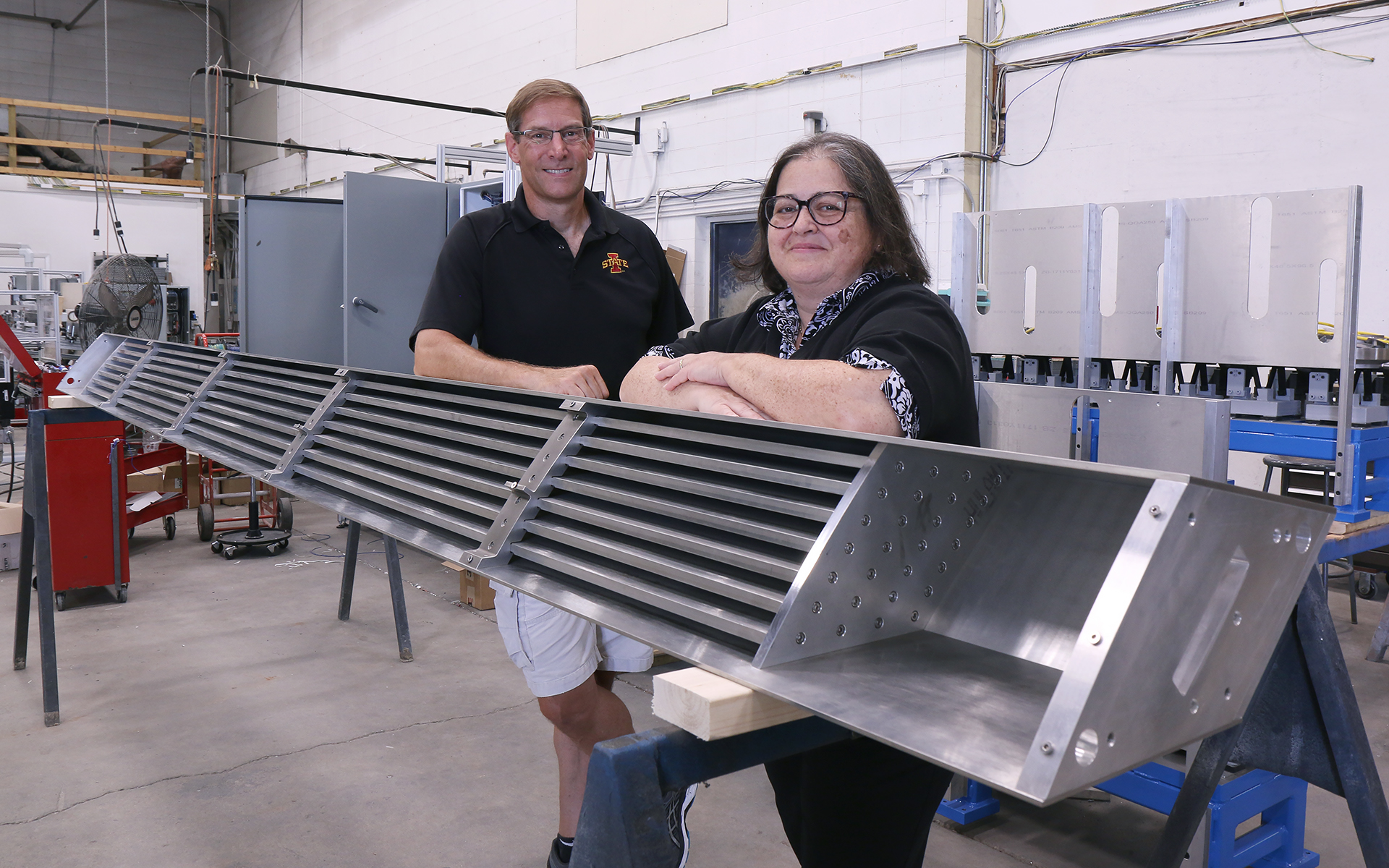 A man and woman stand by metal equipment.