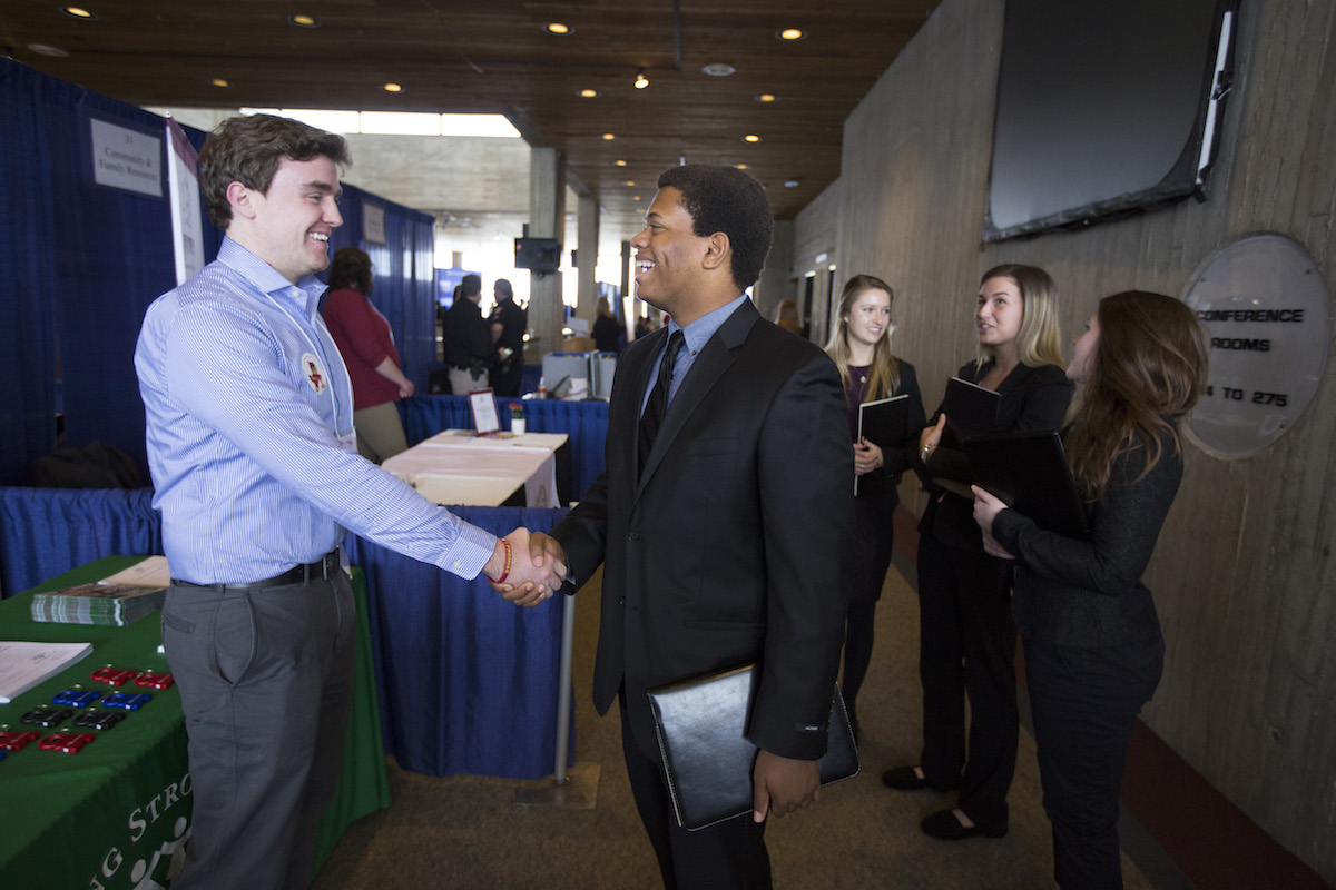 One student shakes hands with a company representative while other students wait.