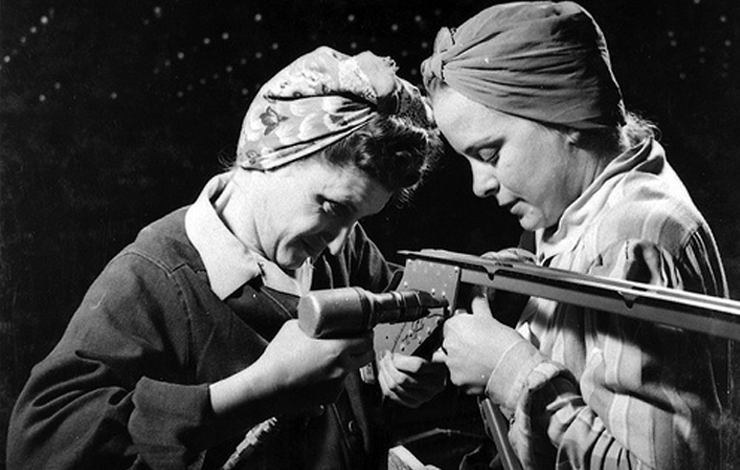 Two women work on a piece of machinery.