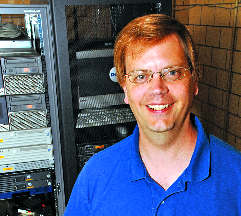 Dr. Tom Holme standing in front of computers.
