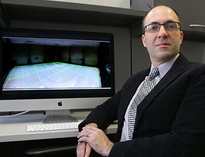 Borzoo Bonakdarpour sitting at computer displaying drone grid image.