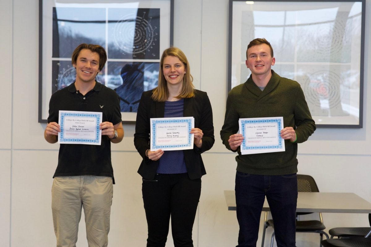 Three students hold certificates after winning the LAS Pitch Competition.