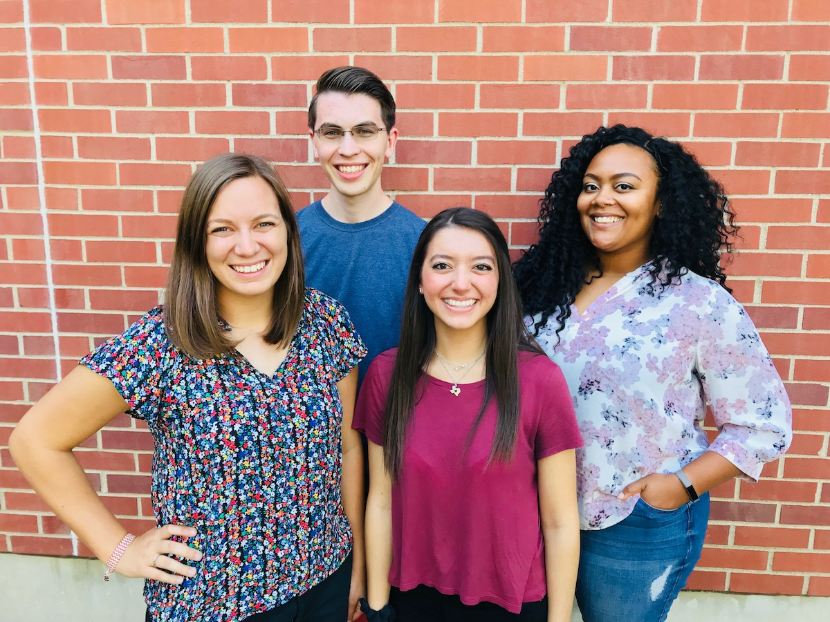 Four college students standing and smiling at the camera