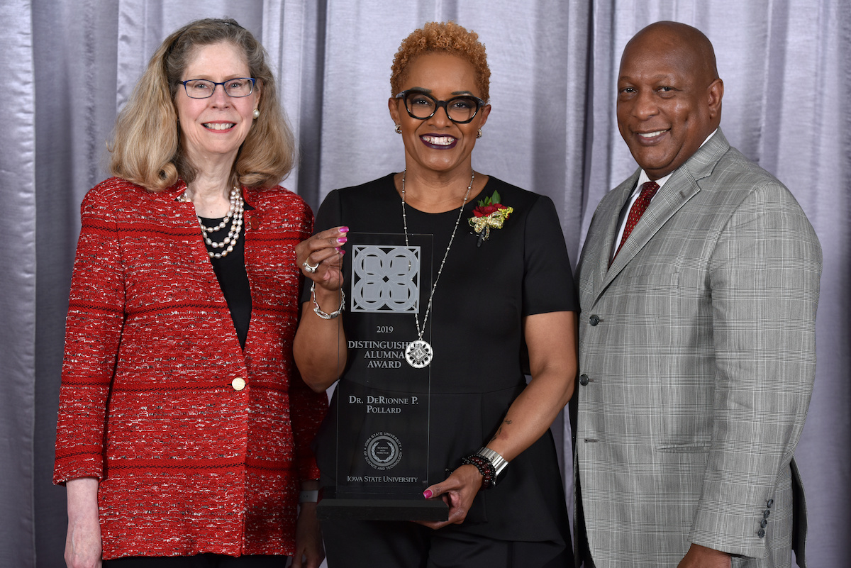 Three people, a while woman with blonde hair, a black woman with short blonde hair and a black man stand smiling at the camera. The woman in the middle holds an award.