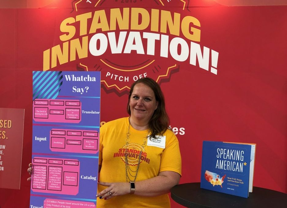 Student holding up display sign with an explanation of an app idea, in front of ISU Standing Innovation backdrop, next to table with book