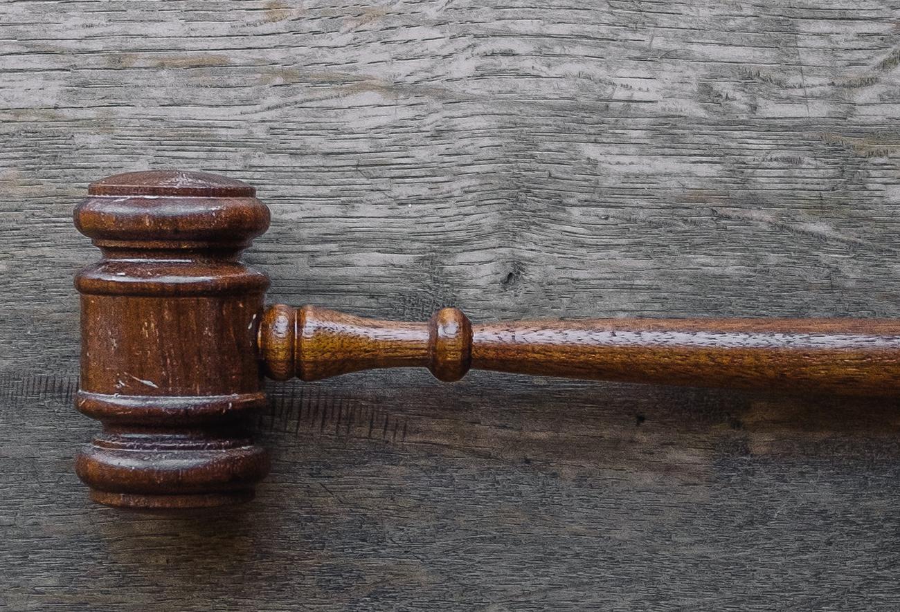 Judge's gavel on wood grain background.