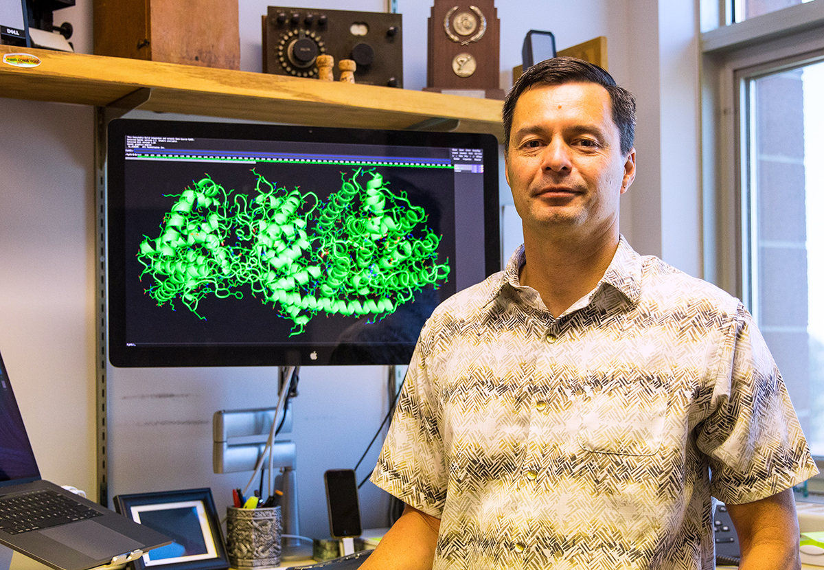 Scientist next to computer monitor with molecular biology images on it