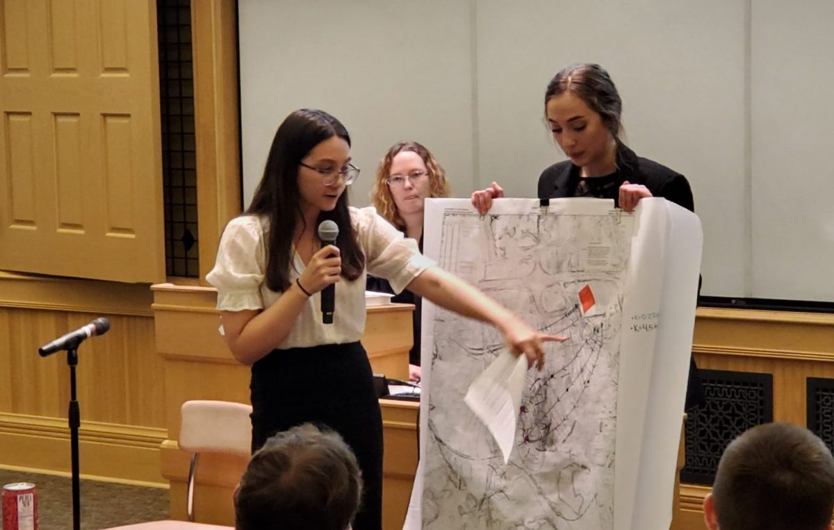 Students enact a mock trial as one points to geographic sketches.