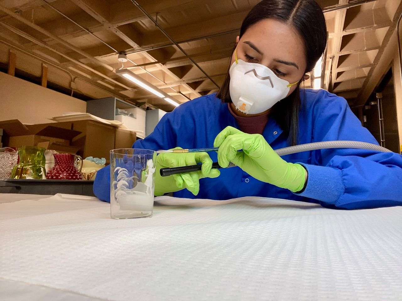Madisyn Rostro cleans a glass museum object