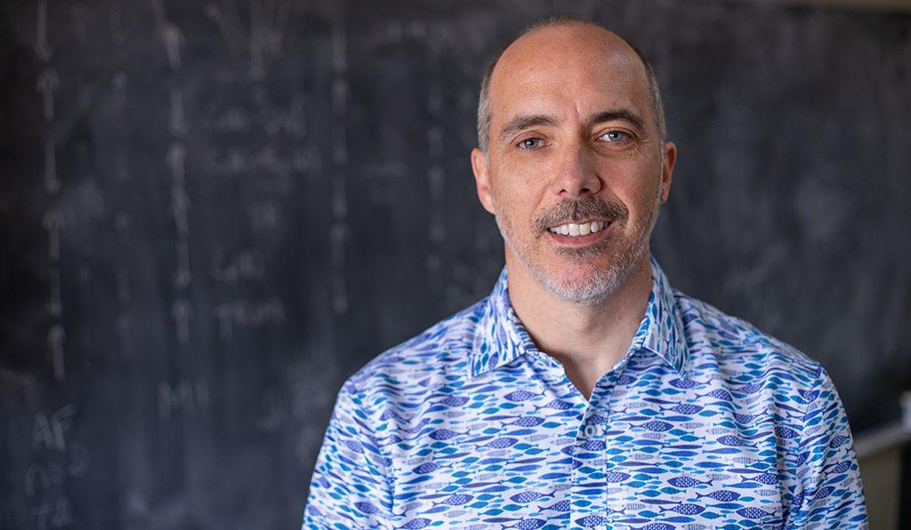 Robert McQueeney stands in front of a classroom blackboard