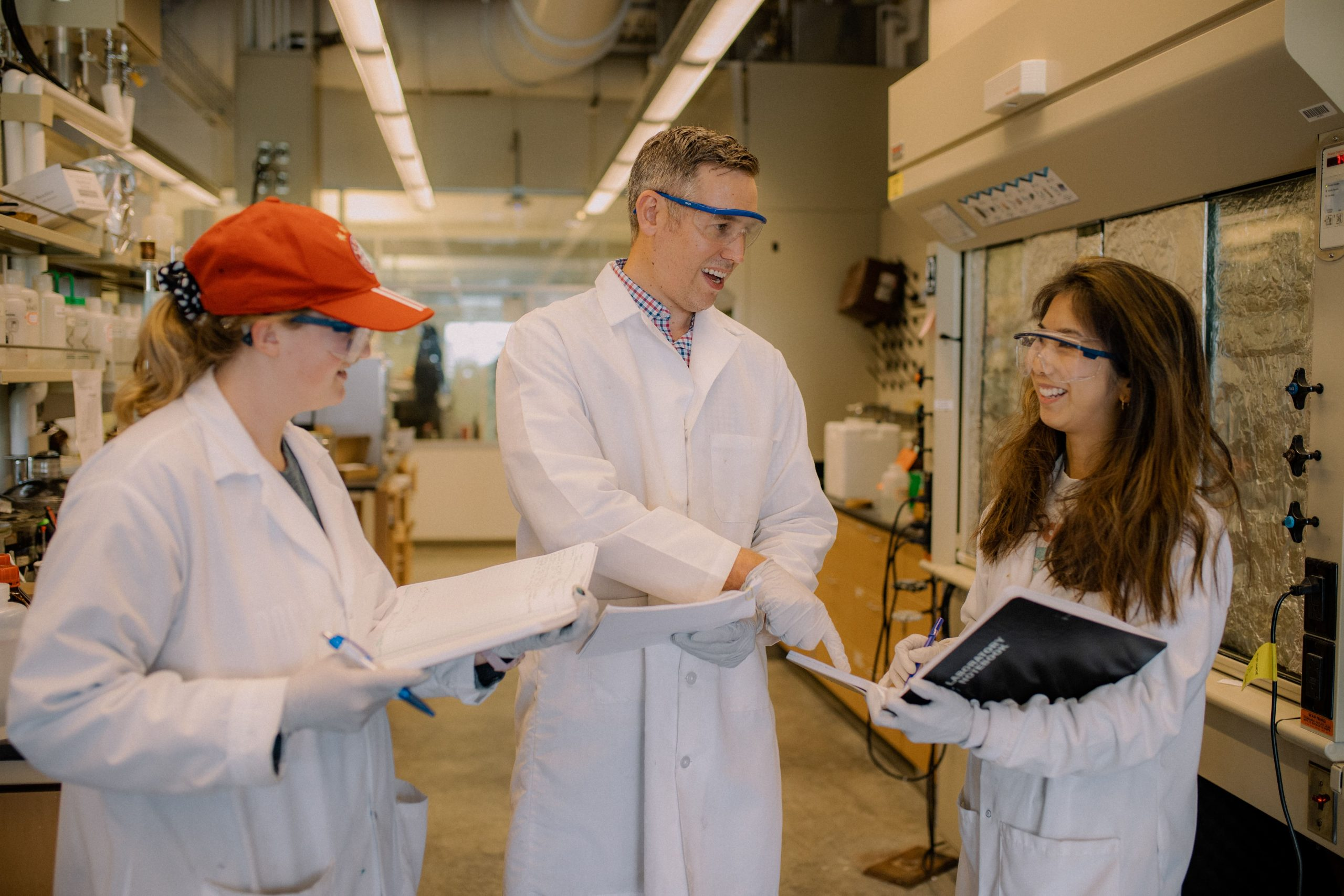 Arthur Winter, professor of chemistry, discusses research in his lab with two female graduate students
