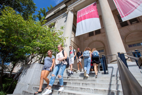ISU students walk down the steps of a campus building on a sunny day