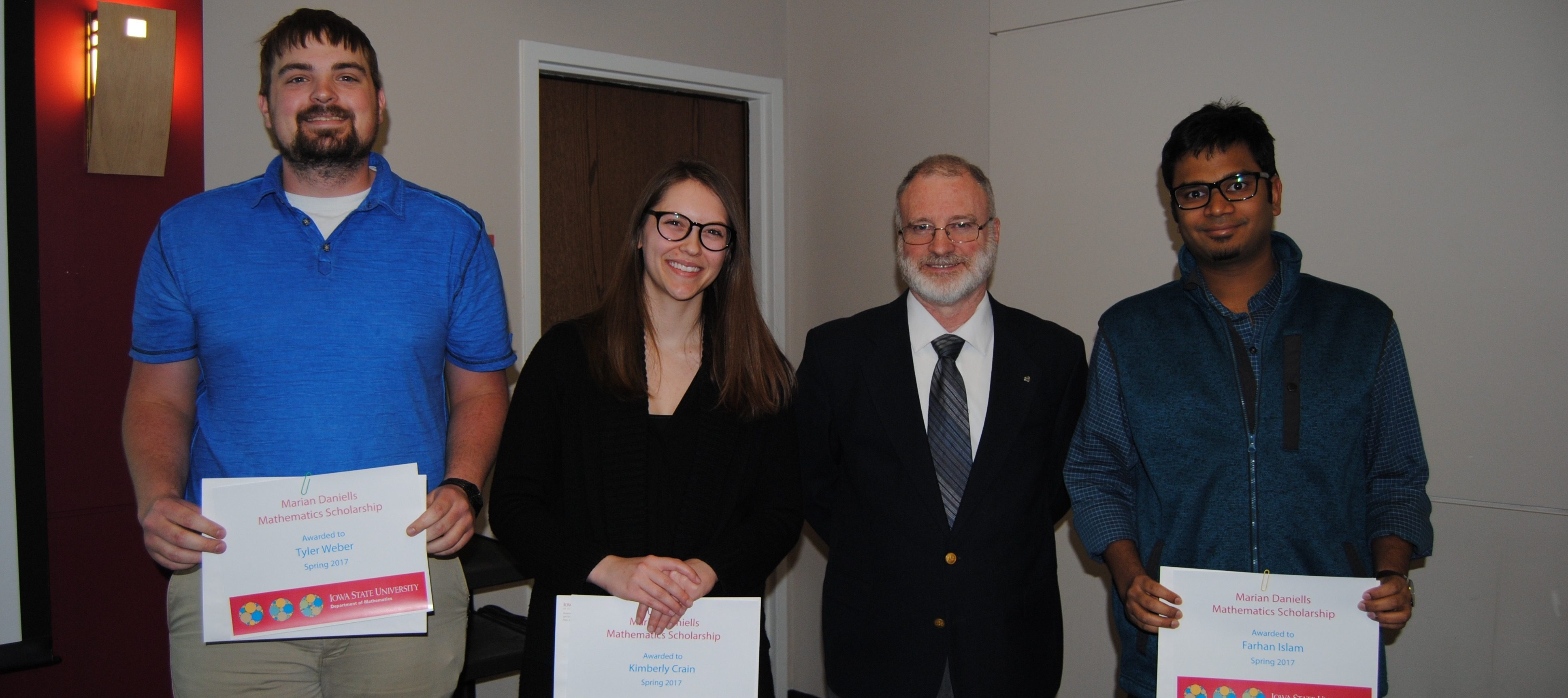James Wilson, director of undergraduate education, presents students Tyler Weber, Kimberly Crain, and Farhan Islam with the Marian Daniells Scholarship.