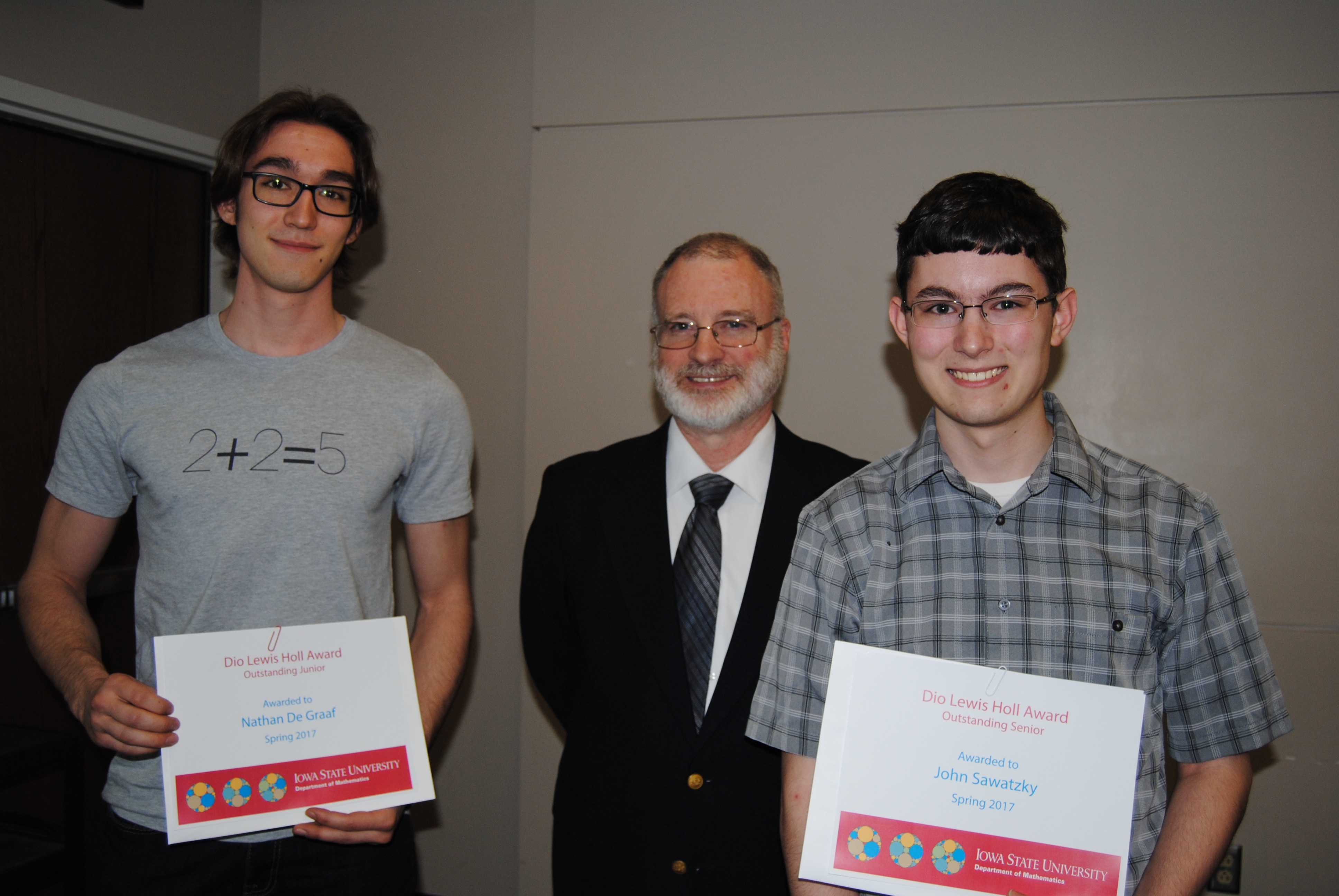 James Wilson, director of undergraduate education presents students Nathan De Graaf and John Sawatzky with Dio Lewis Holl Awards.