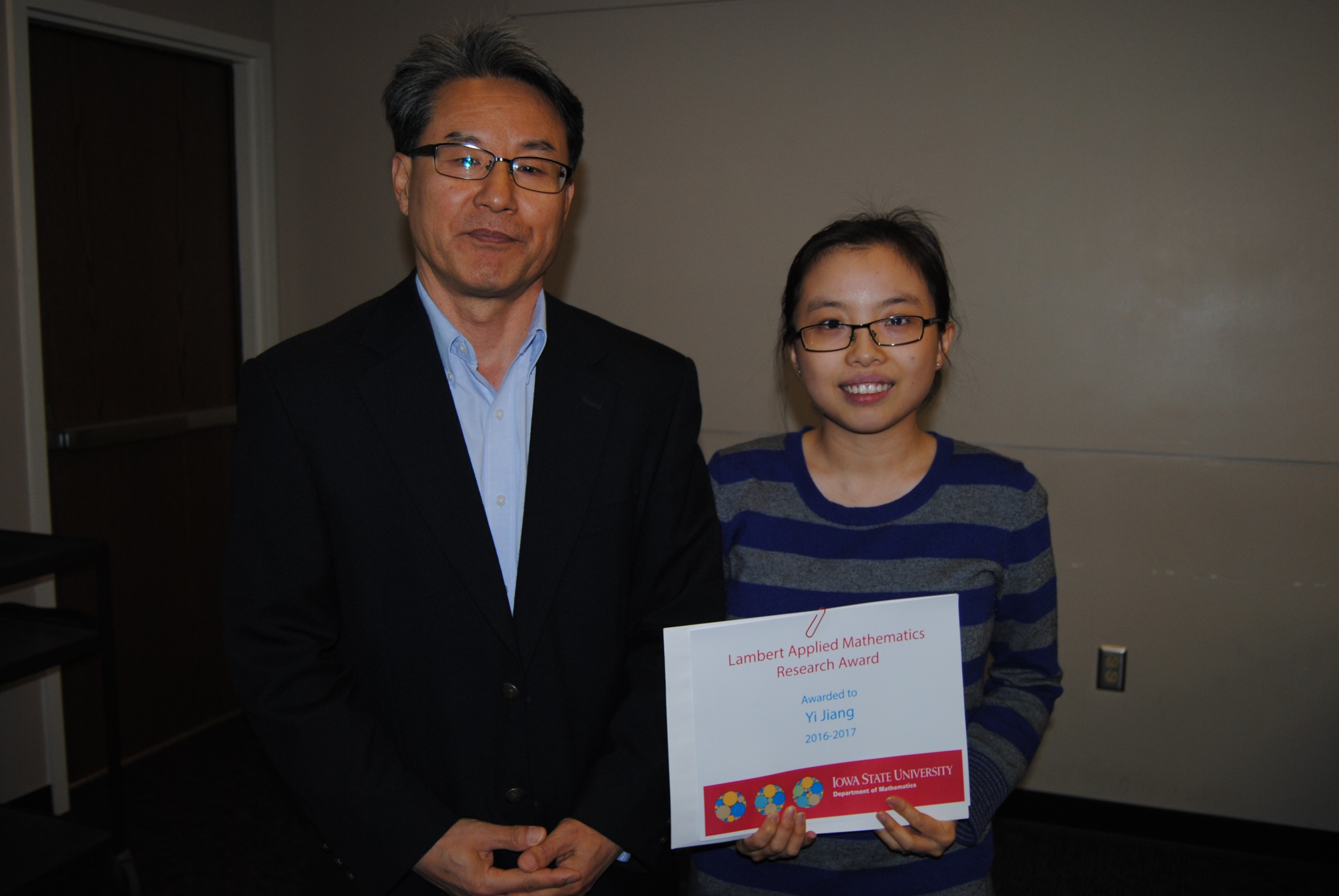 "Sung-Yell Song presents Yi ""Jacky"" Jiang with a certificate for the Lamber Applied Mathematics Research Award."