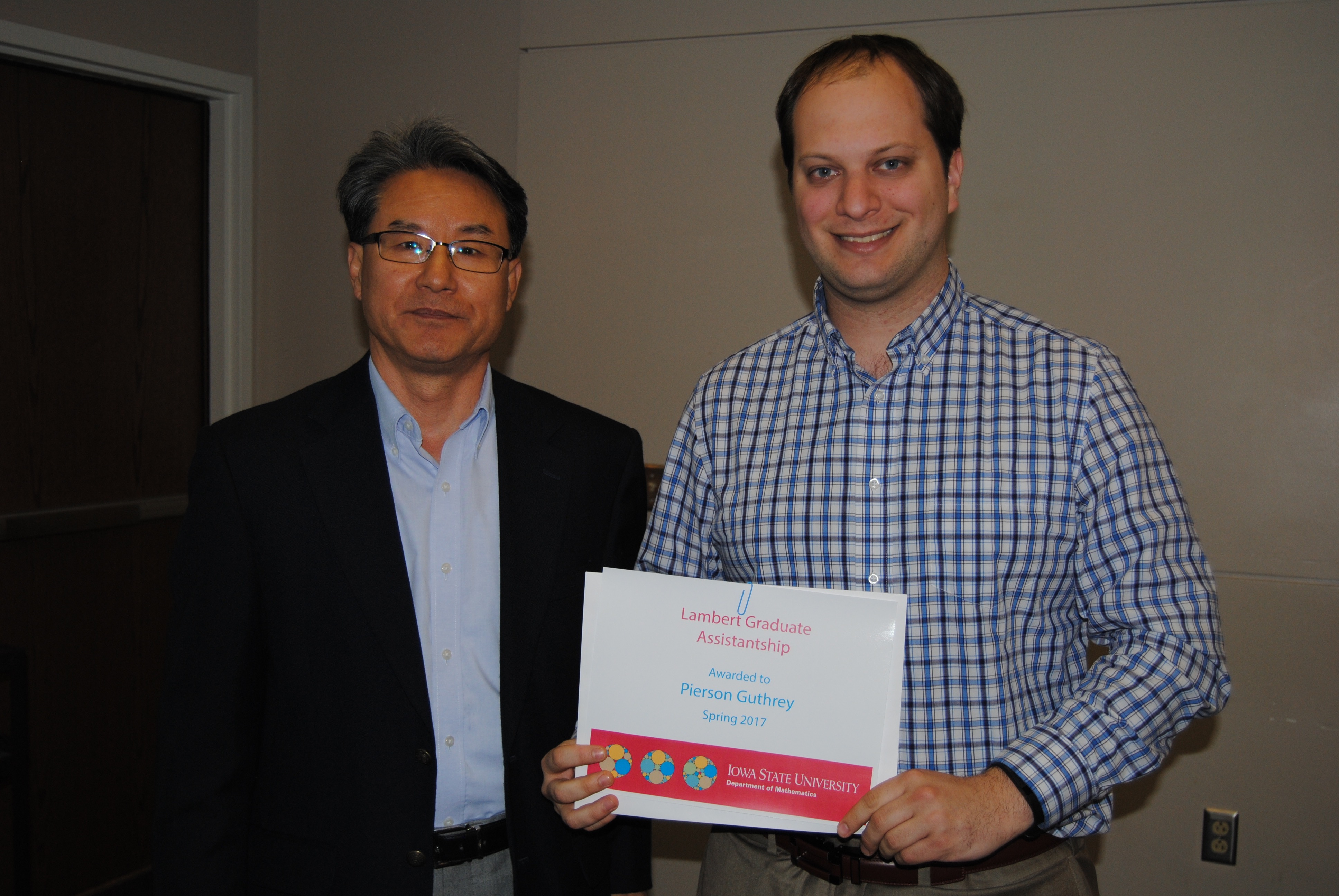 Sung-Yell Song, associate professor of mathematics, presents graduate student Pierson Guthrey with a certificate for the Lamber Graduate Assistantship.
