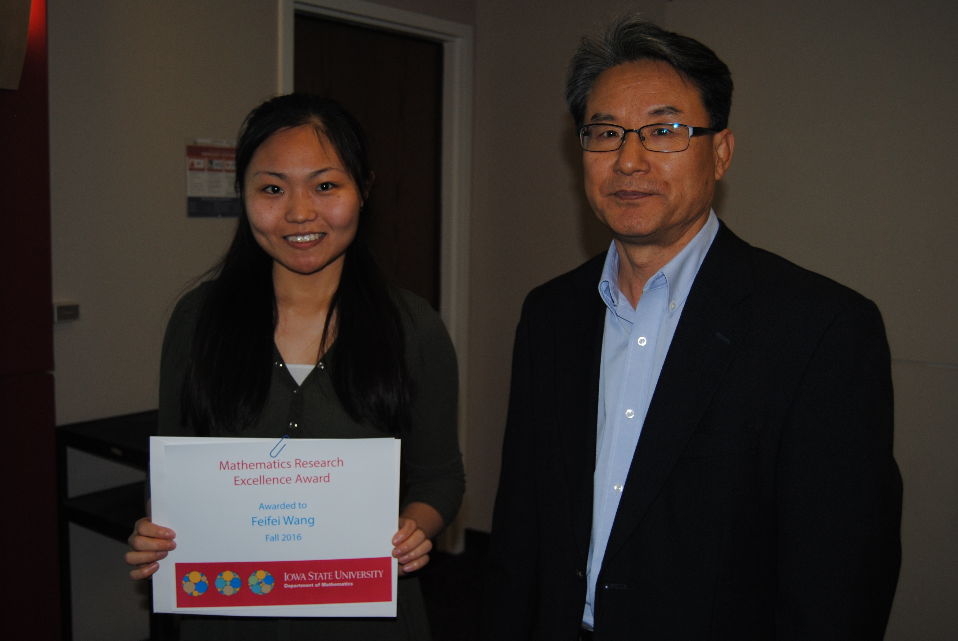 Sung-Yell Song, associate professor of mathematics presents graduate student Feifei Wang with a certificate for the Mathematics Research Excellence Award.