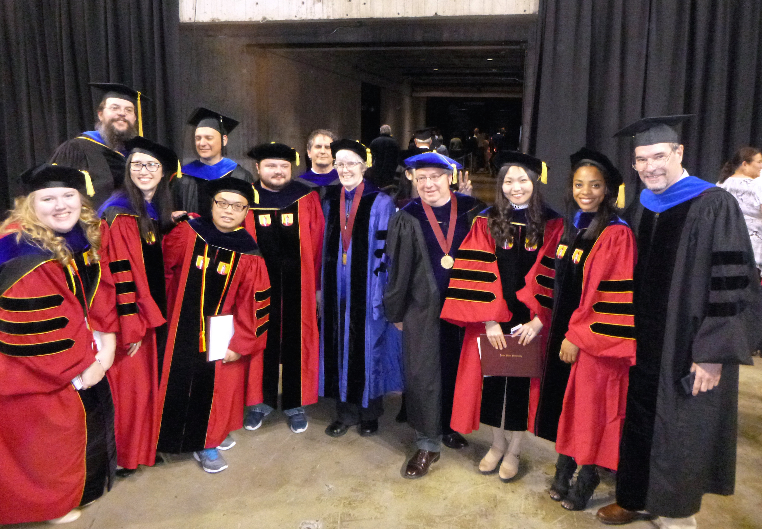 Graduate students and faculty pose in Hilton Coliseum at graduation.