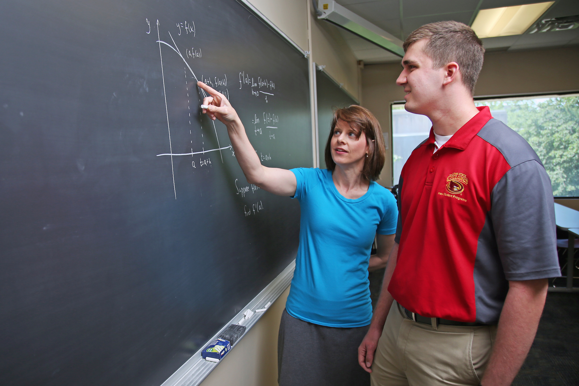 Heather Bolles, senior lecturer in mathematics, stands at a blackboard with a student, explaining the definition of derivative at a point of the graph.
