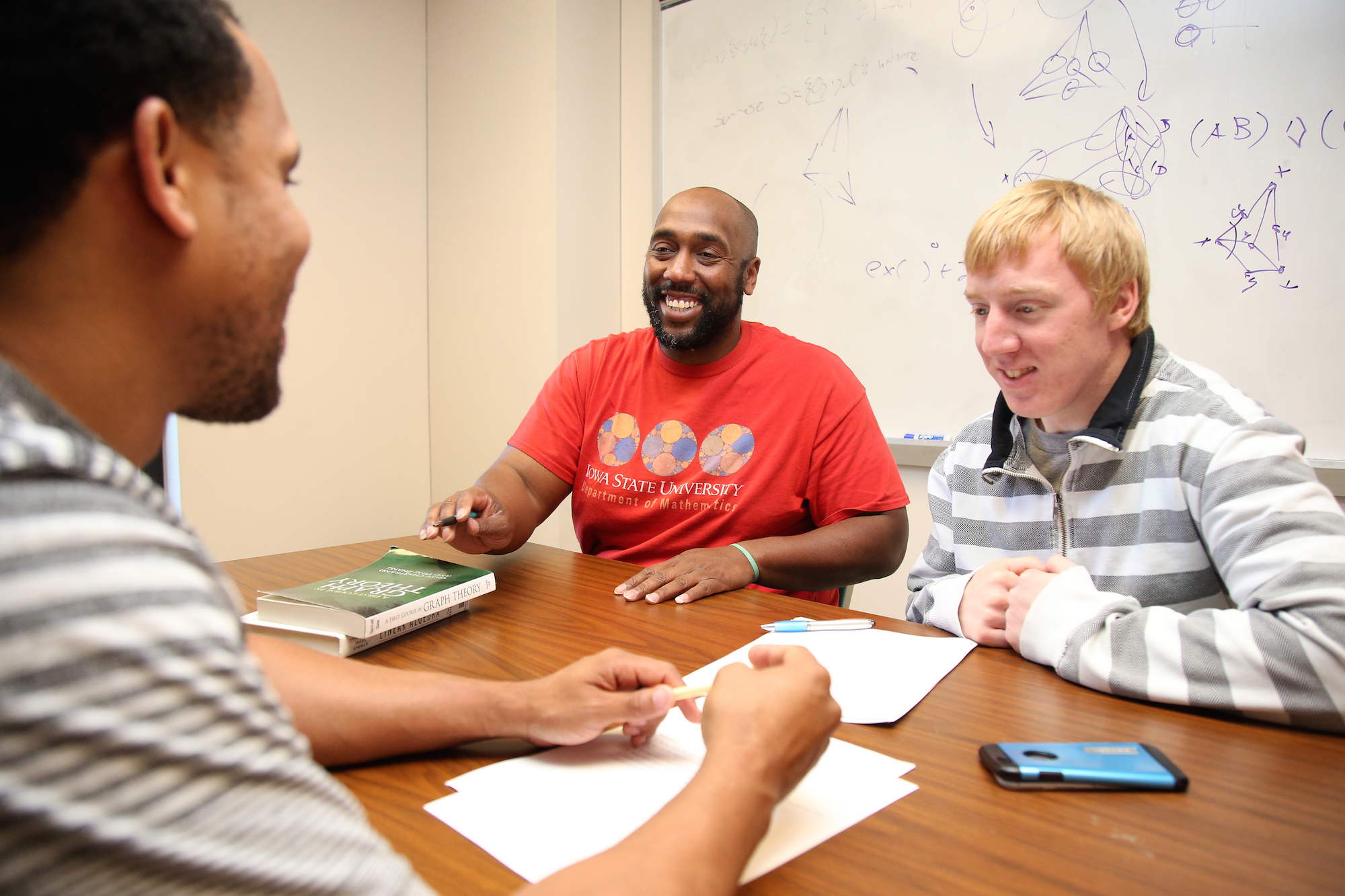 Michael Young, assistant professor of mathematics, in his office at a table working on math problems with graduate students Derek Young and Alex Schulte.