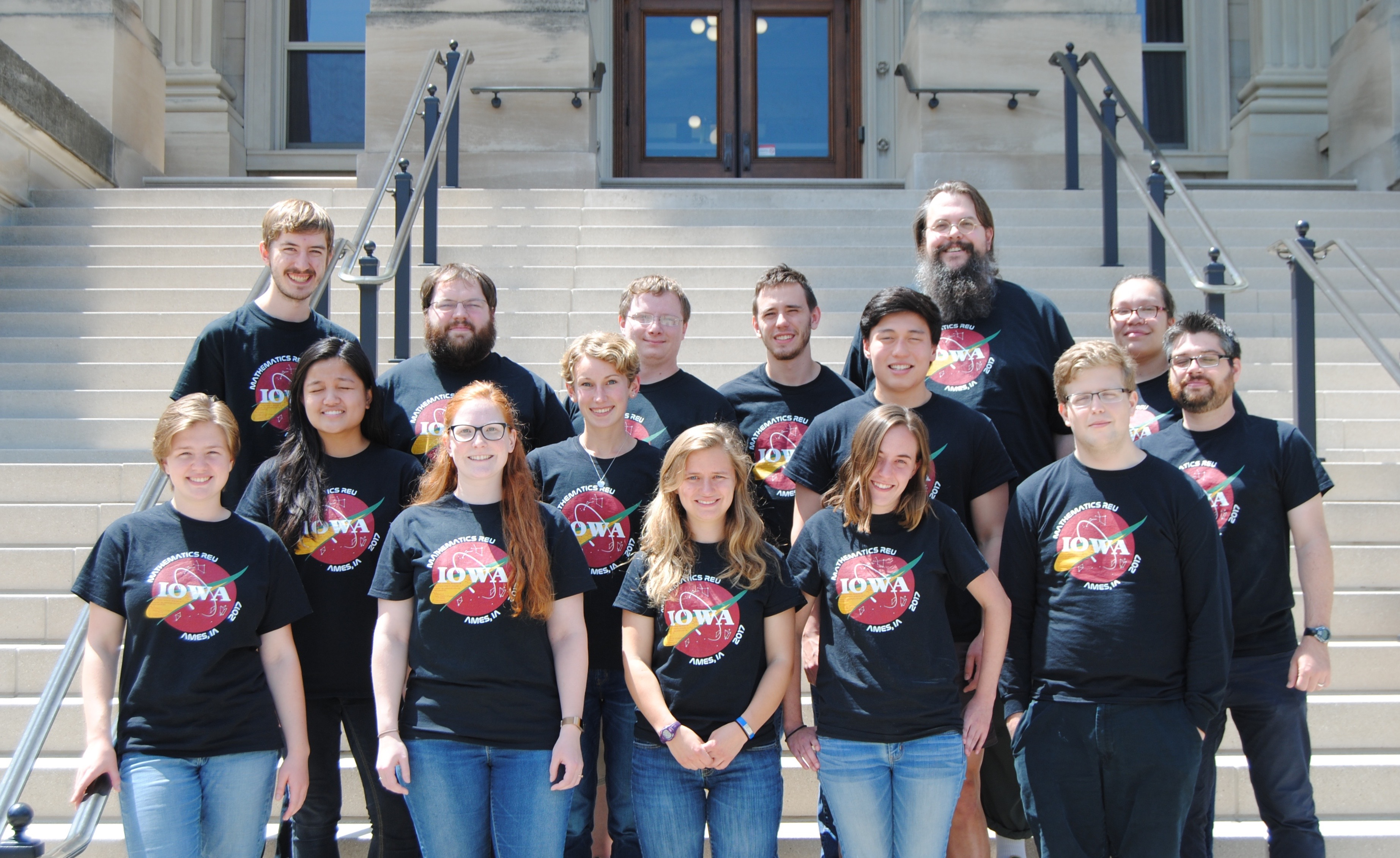 Students from the Mathematics Research Experience for Undergraduates pose on the steps of Beardshear Hall with faculty James Rossmanith and Steve Butler.
