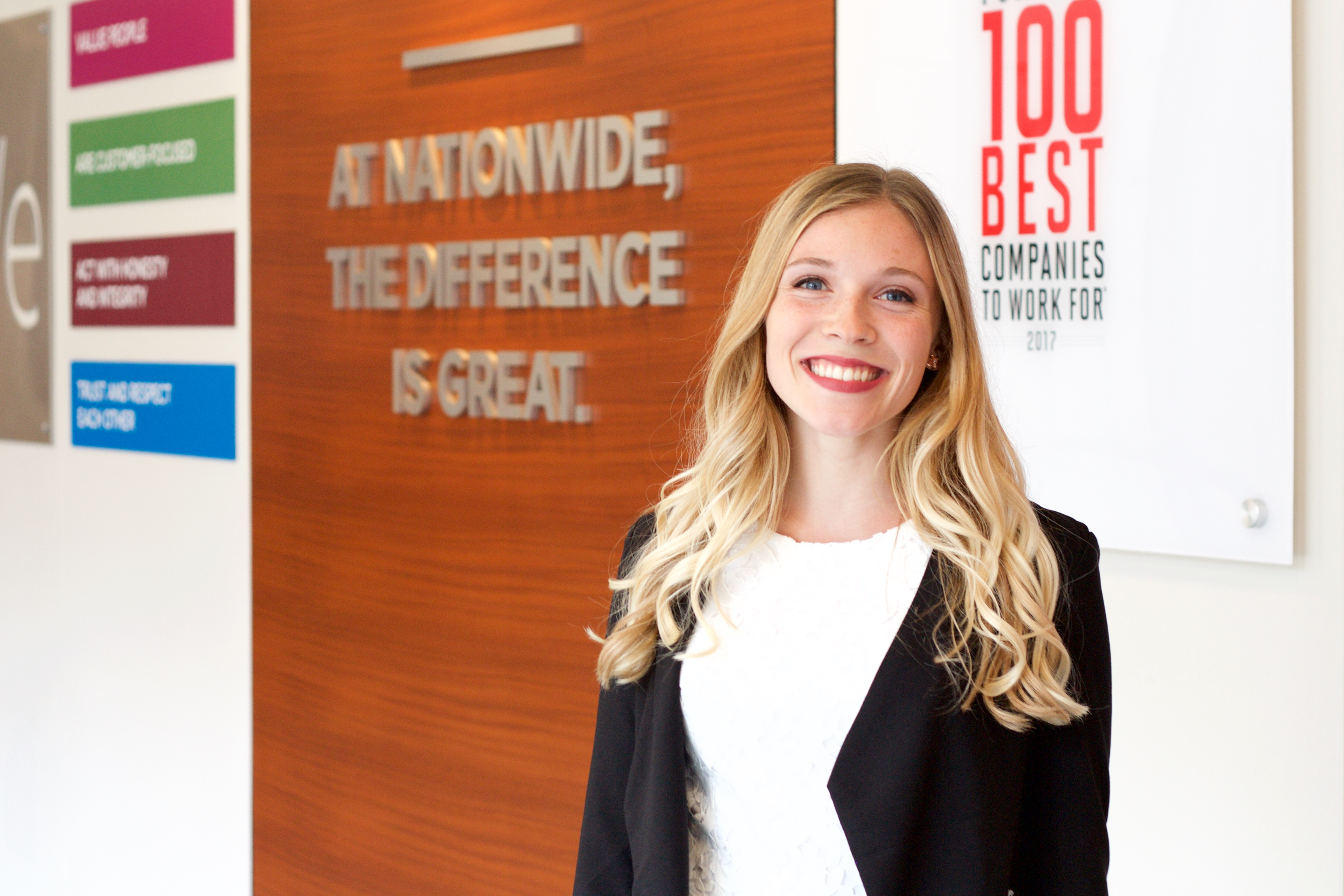 Undergraduate student Aimee Rodin poses at her internship at Nationwide Insurance Company. On the wall behind her the company has a sign that it is part of 100 Best Companies to Work For.