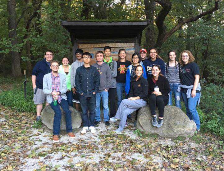 Students in the Mathematics and Statistics Learning Community pose at a park in front of the woods.