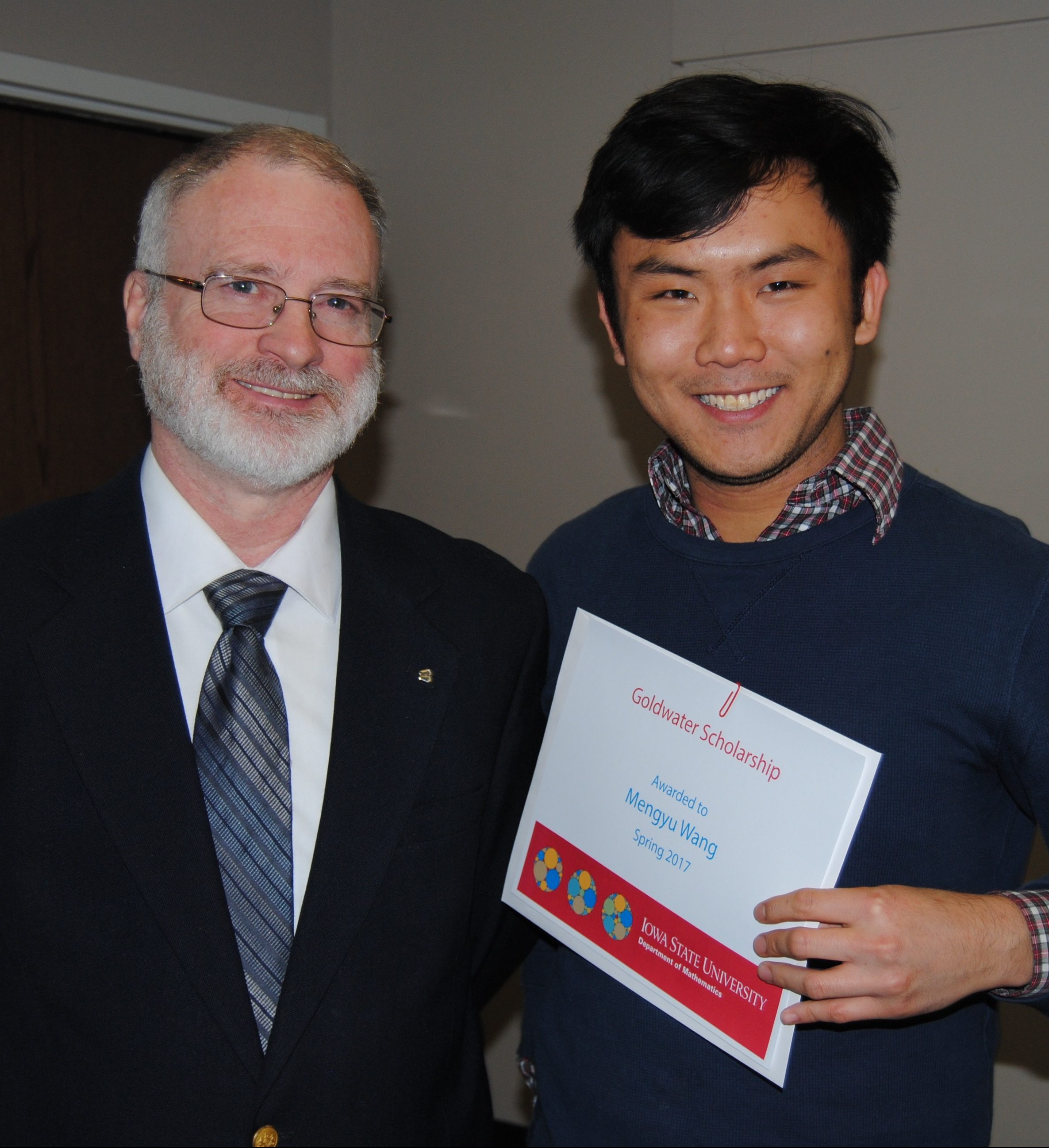"""Student Mengyu """"Allen"""" Wang receiving a certificate from James Wilson, director of undergraduate education in mathematics, in honor of receiving the Goldwater scholarship."""