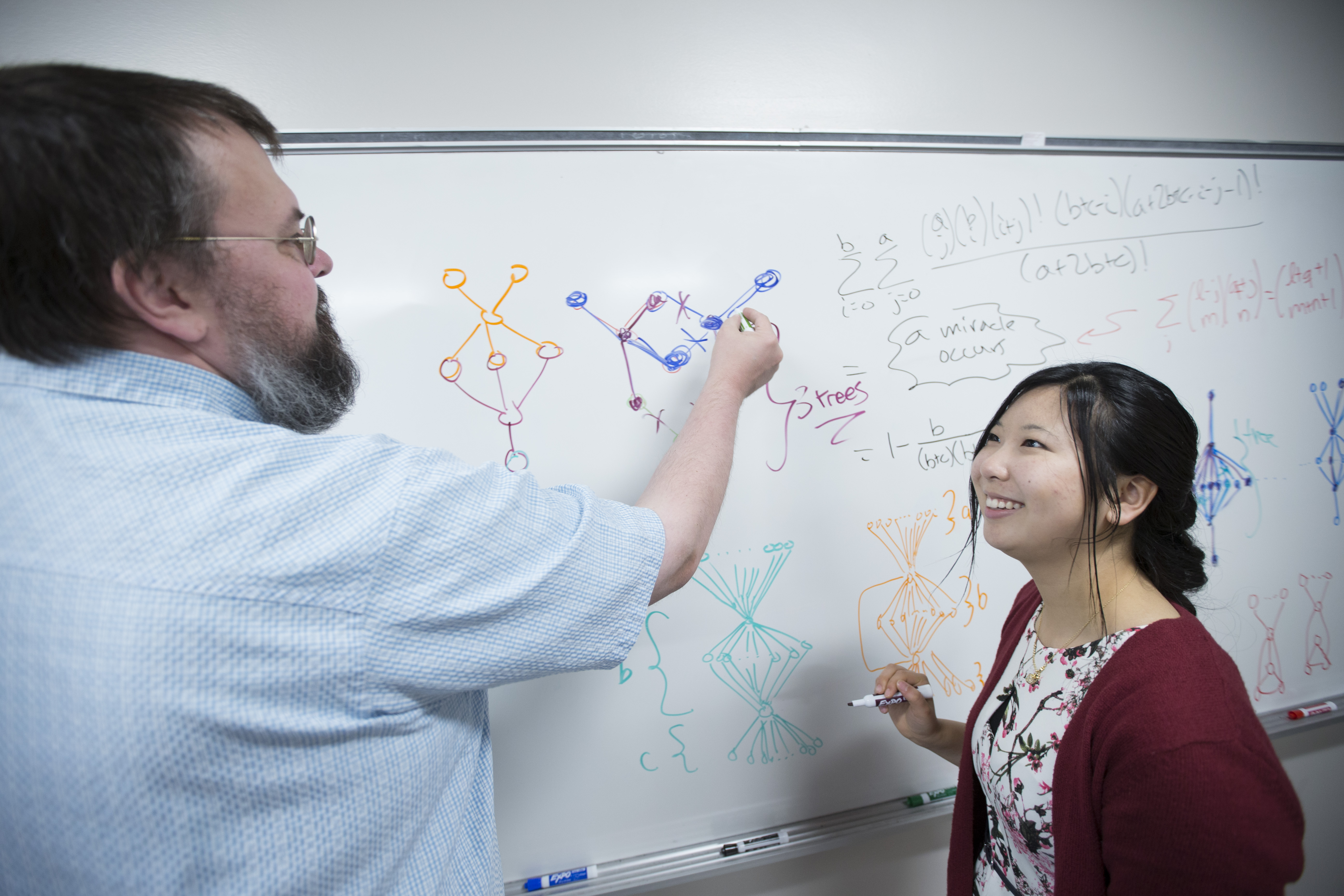 A math professor and female student at a whiteboard.