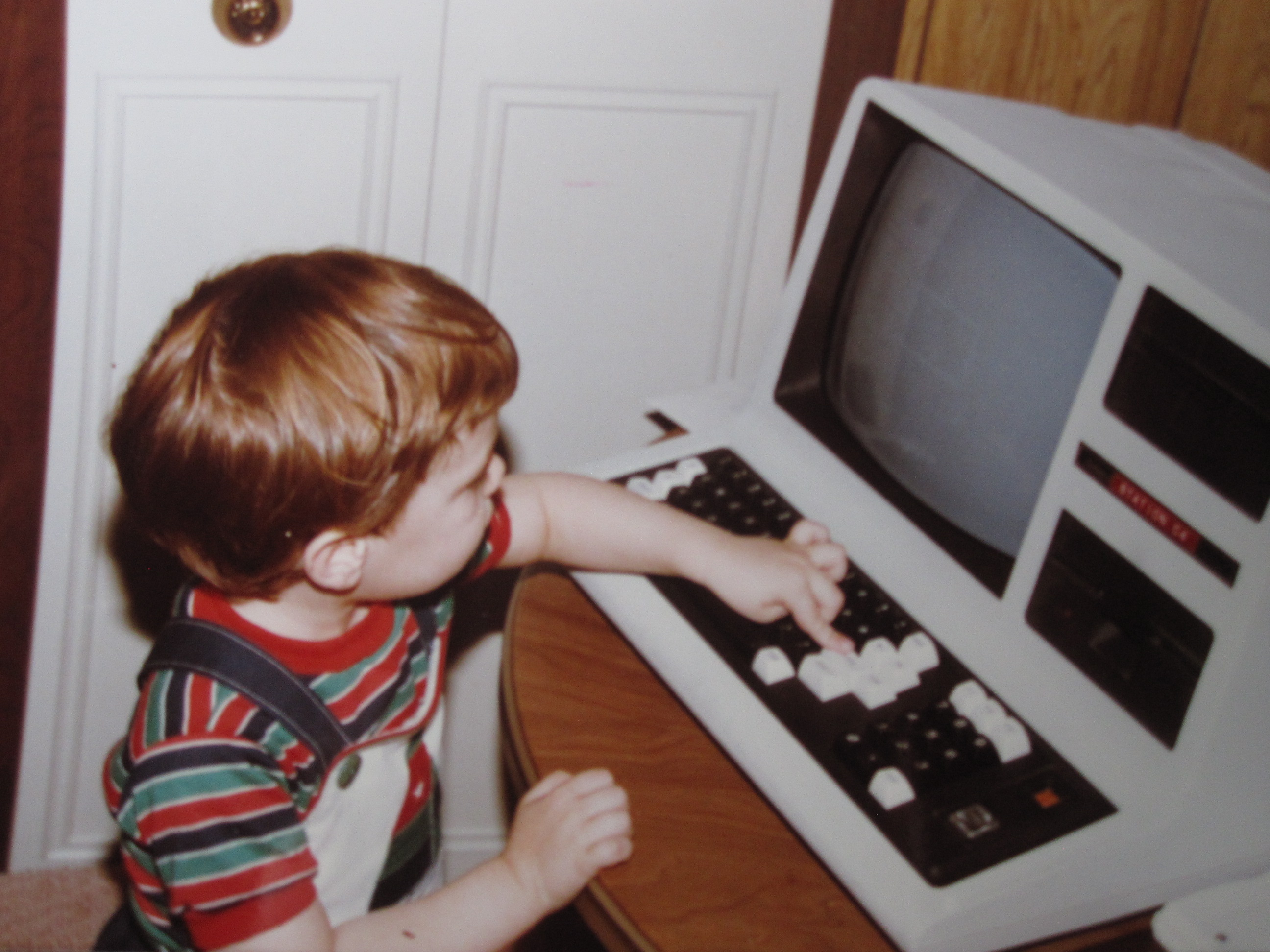 A boy looking at an old computer.