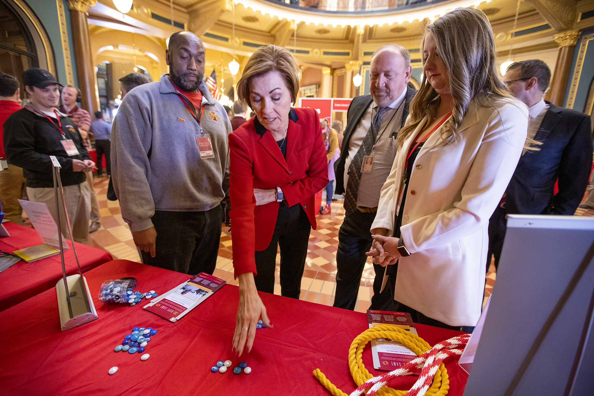 Michael Young shows Gov. Kim Reynolds how to play an interactive math game