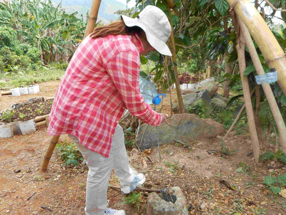 Dr. Rose Caraway in Cuba's second largest city, Santiago de Cuba, washing her hands using a recycled water bottle as part of her research on permaculture ethics.