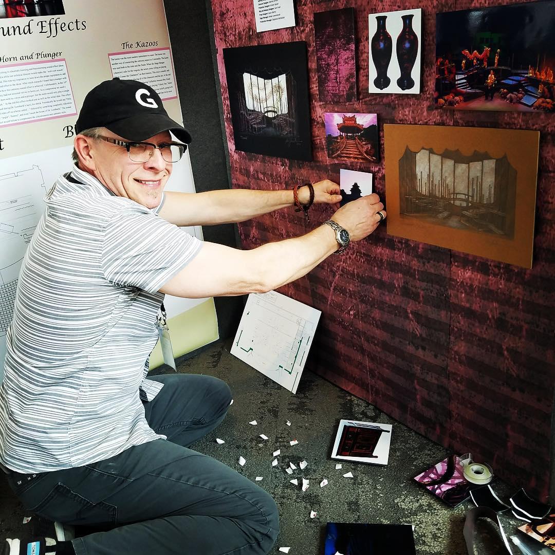 Man putting up photos on wall