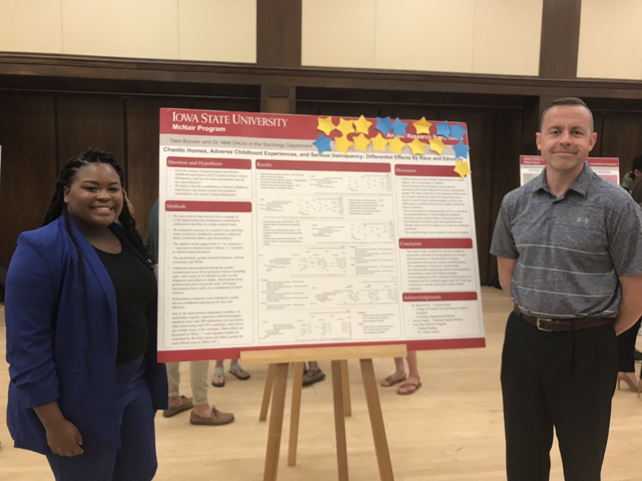 Young black woman and white man with academic research poster